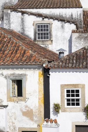 Portugal, Obidos. Ancient, red, terra cotta tiled roof tops, lines.