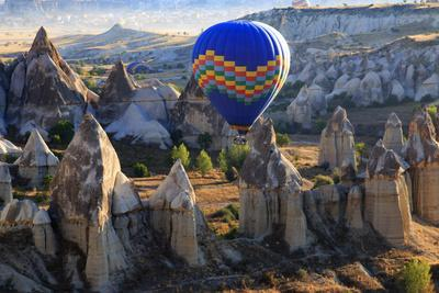 Turkey, Anatolia, Cappadocia, Goreme. Hot air balloons flying above the valley.