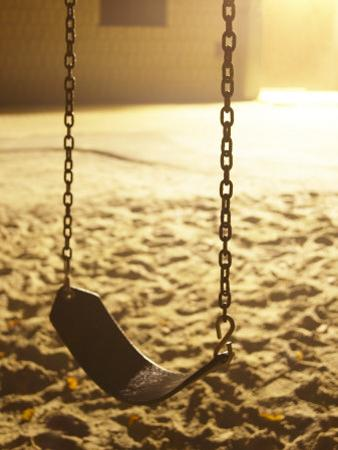 Empty Childrens Swing in a Playground Illuminated at Night
