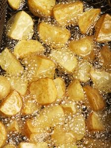 Potatoes Being Fried in Hot Oil by Enrique Chavarria