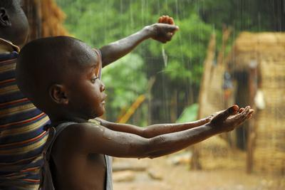 A Bassari Child Holding Out Hands to Collect Rainwater, Bassari Country, East Senegal
