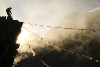 Climber on Kala Pattar Peak (5545M) with Buddhist Prayer Flags at Sunset, Nepal, Himalaya