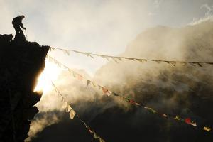 Climber on Kala Pattar Peak (5545M) with Buddhist Prayer Flags at Sunset, Nepal, Himalaya by Enrique Lopez-Tapia