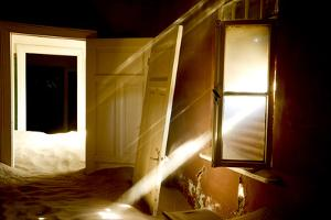 Light Streaming Through Window On Sand Covered House In Kolmanskop Ghost Town by Enrique Lopez-Tapia