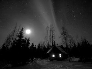 Cabin under Northern Lights and Full Moon, Northwest Territories, Canada March 2007 by Eric Baccega