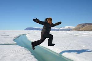 Young Inuit Boy Jumping over a Crack on Ice Floe, Ellesmere Island, Nanavut, Canada, June 2012 by Eric Baccega