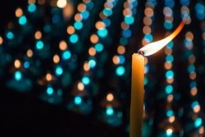 A Candle with Flame in Front of Rows of Other Candles by Eric Kruszewski
