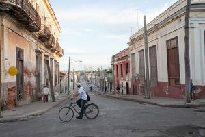 A Man Rides a Bicycle on the Street Through an Intersection in Downtown Cienfuegos by Eric Kruszewski