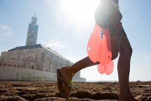 In Front of Casablanca's Hassan Ii Mosque, a Young Boy Carries Flippers for Swimming and Diving by Eric Kruszewski