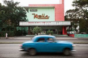 In Havana, a View of a Theater and Classic American Car by Eric Kruszewski