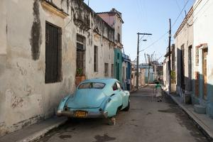 On a Street in Downtown Havana, a Classic American Car Rests on a Cinder Block as a Woman Walks By by Eric Kruszewski