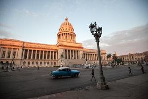 People Walk the Streets and a Classic American Car Drives Past the El Capitolio Building, Havana by Eric Kruszewski