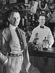 21 Club's Jack Kriendler Relaxing at Bar with Drink, Bartender Holding Bottle on Other Side of Bar by Eric Schaal