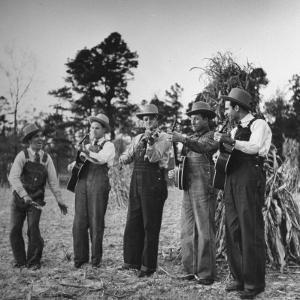 Five Male Musicians Dressed in Hats and Bib Overalls Standing in a Field by Eric Schaal
