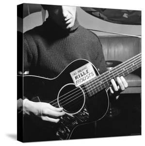 Folk Singer Woody Guthrie Playing Guitar with Sign on It Reading This Machine Kills Fascists by Eric Schaal