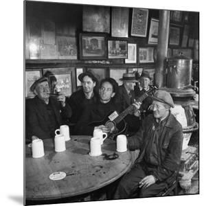 Woody Guthrie Playing and Singing for Patrons of Mcsorley's Bar by Eric Schaal