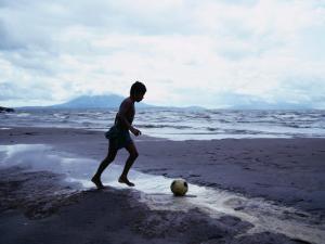 Boy Kicking Soccer Ball on Beach, Lake Nicaragua, Granada, Nicaragua by Eric Wheater