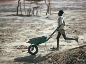 Boy Running with Wheelbarrow, Burkina Faso by Eric Wheater