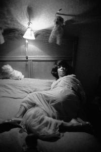 Surrounded by toy-animals, a Berlin stripper settles down for a quiet night. by Erich Lessing