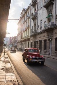 Vintage Cars Drive Down a Street in Havana by Erika Skogg