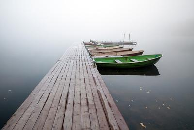 Autumn. Small Pier with Boats on Lake in Cold Still Foggy Morning