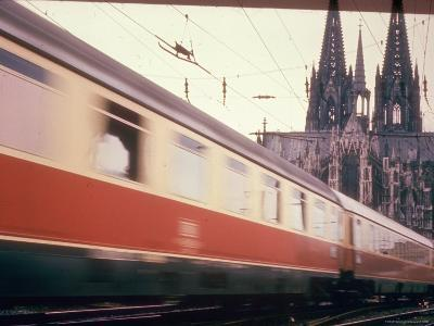 Eurailpass in Europe: Germany's Parsifal Express Speeding Past Cologne Cathedral-Carlo Bavagnoli-Photographic Print