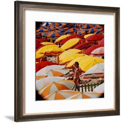 Europe Beach Scene Crowded with Colorful Umbrellas and a Bikini-Clad Young Woman-Ralph Crane-Framed Photographic Print
