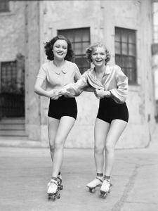 Portrait of Two Young Women with Roller Blades Skating on the Road and Smiling by Everett Collection