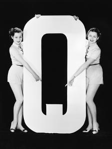Two Women Pointing at Huge Letter Q by Everett Collection
