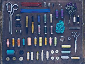 Vintage Set of Designer Clothes on a Dark Background among Buttons by Evgeniya Porechenskaya