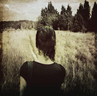 Woman Following Trail in Field