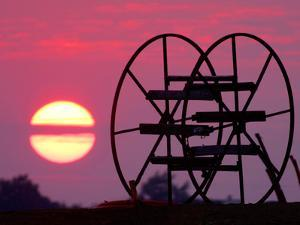 Farm Equipment is Silhouetted by a Setting Sun