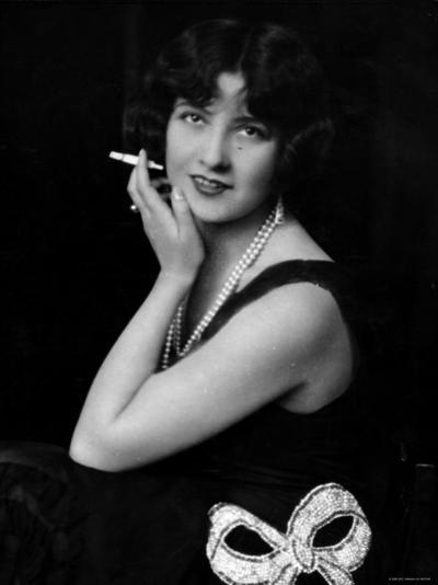 Fashionable Woman with Cigarette Holder in Hand Wearing Long Double Strand Pearl Necklace--Photographic Print