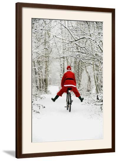 Father Christmas Riding Bicycle in Snowy Woodland Path--Framed Photographic Print