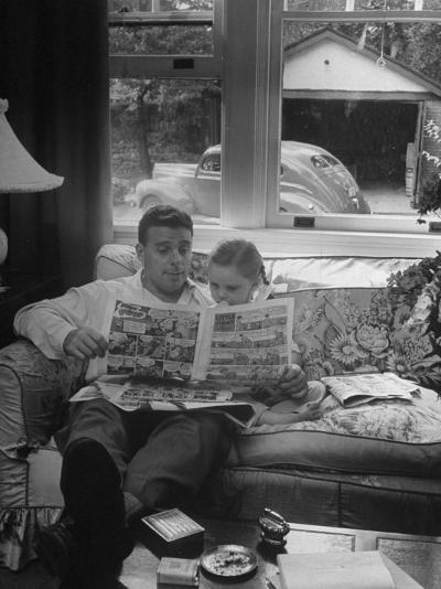 Father Sitting on Couch with Pigtailled Daughter Reading to Her the Sunday Comic Pages-Nina Leen-Photographic Print
