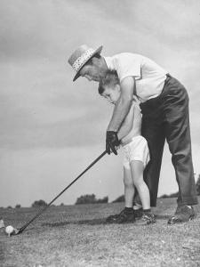 Father Teaching His Small Son How to Play Golf