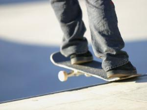 Feet on a Skateboard at the Edge of a Ramp