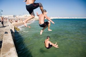 Children Jumping into the Sea from Stone Jetty by Felipe Rodriguez