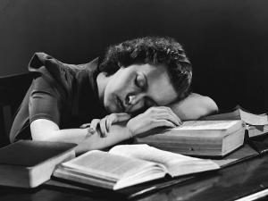 Female College Student Asleep on Open Books at Her Desk