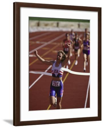 Female Runner Victorious at the Finish Line in a Track Race--Framed Photographic Print