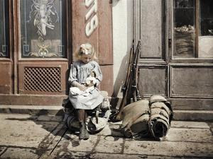 A Little Girl Playing with Her Doll; Two Guns and a Knapsack are Next to He by Fernand Cuville