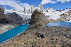 A couple in mountain gear rests on rocks with view to Lago de los Tres and Mount Fitz Roy, Patagoni by Fernando Carniel Machado
