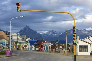 Colourful houses on touristic road framed by traffic lights post with snowy mountain chain beyond,  by Fernando Carniel Machado