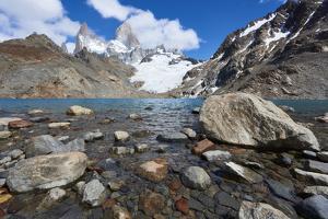 Stones seen through the water of Lago de los Tres featuring Monte Fitz Roy in the background. Monte by Fernando Carniel Machado