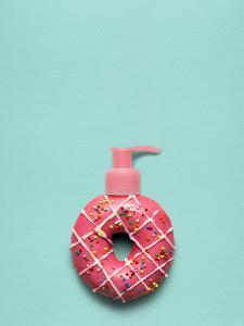 Creative Still Life of a Tasty Sweet Donut with a Cosmetic Pump Dispenser on Blue Background by Fisher Photostudio