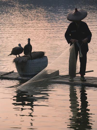 Fisherman Fishing with Cormorants on Bamboo Raft on Li River at Dusk, Yangshuo, Guangxi, China-Keren Su-Photographic Print