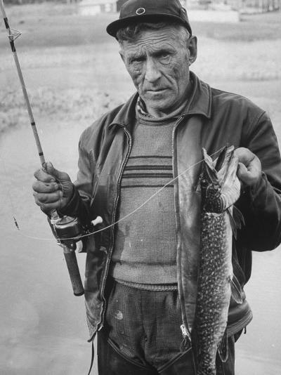Fisherman Lauri Rapala, Who Handmakes Fishing Lures, with a Fish He Caught--Photographic Print