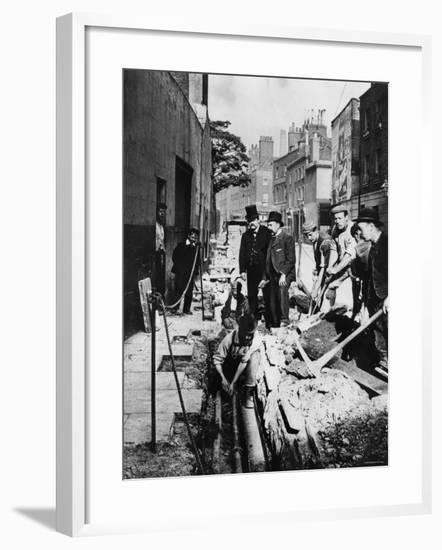 Fixing a Pipe--Framed Photographic Print