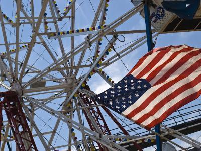 Flag in Front of a Ferris Wheel Against a Summer Sky-Todd Gipstein-Photographic Print