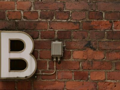 Florescent B Letter Light on Brick Wall--Photographic Print